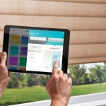 person using Hunter Douglas app on tablet to control blinds
