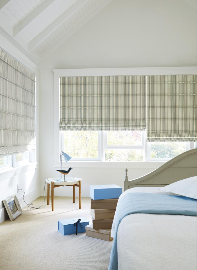 Hunter Douglas Design Studio Roman Shades in a blue bedroom